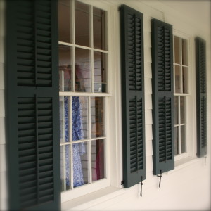 Wavy glass-paned windows with beautiful old wooden shutters and iron shutter stays.